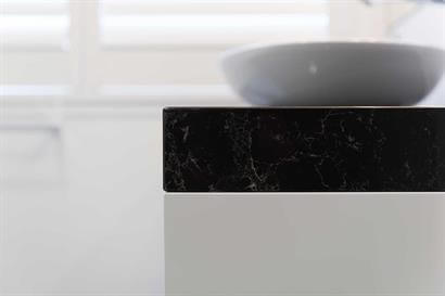 Gloss white bathroom cabinet with dark marble-effect benchtop and oval basin
