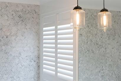 Pendant bathroom lighting complementing neutral grey tiles and plantation shutters by Adelaide Bathrooms