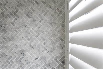 Bathroom wall tiles in classic herringbone pattern against white plantation shutter