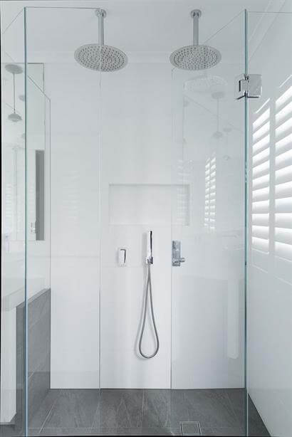 Large frameless shower with twin overhead roses and streamlined wall inset