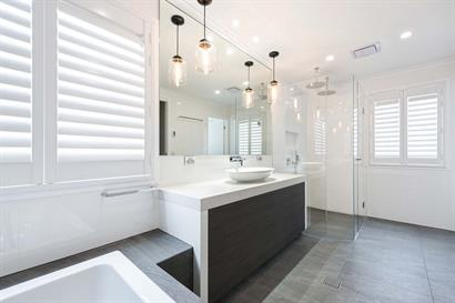 Large contemporary bathroom filled with natural light and warm, neutral tones