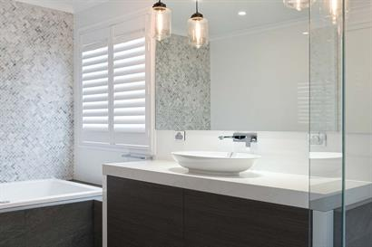 Luxury bathroom in shades of grey with warm timber grains and modern lighting