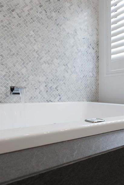Elegant waterfall tap filling spa bath in luxury bathroom