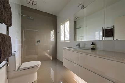 Subtle bathroom lighting mounted under floating high-gloss cabinets