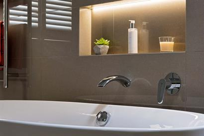 Intimate bathroom mood lighting with backlit wall inset