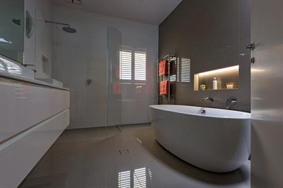 Contemporary freestanding bath with backlit wall inset