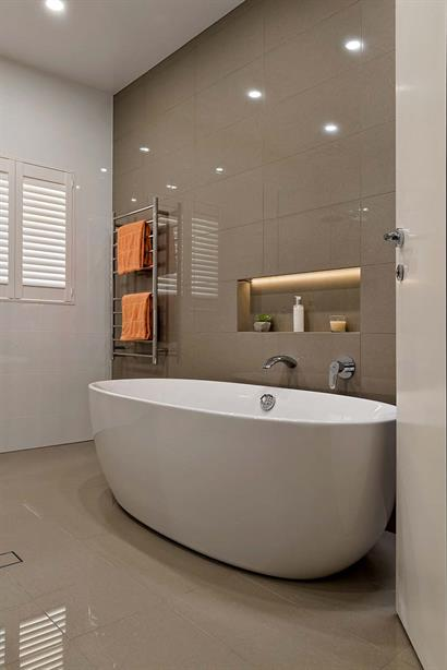 Contemporary bathroom with deep oval bath and floor-to-ceiling tiles