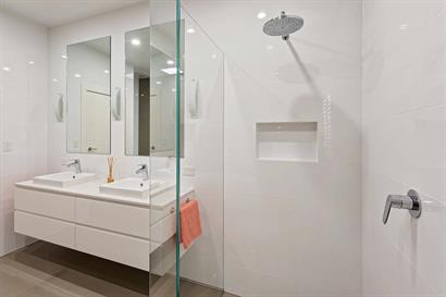 Double basins on floating cabinets and frameless shower with  wall inset
