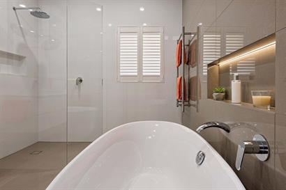 Freestanding oval bath and frameless corner shower with wall insets