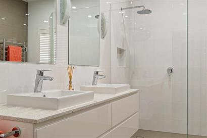 Convenient twin basins set in stone benchtops and white gloss cabinets