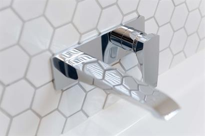 Modern tap and mixer set wall-mounted over bath against classic white hexagonal wall tiles