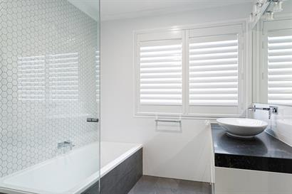Small modern bathroom with plantation shutters, contemporary tiling and marble effect benchtop