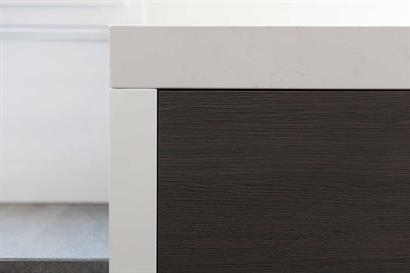 Gloss white bathroom cabinet with off-white stone benchtop and timber grain drawers