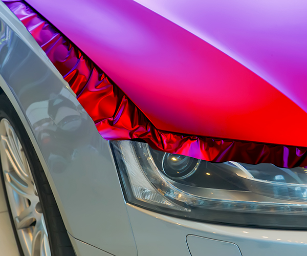 brightly colored vinyl car wrap being applied to the hood of the car