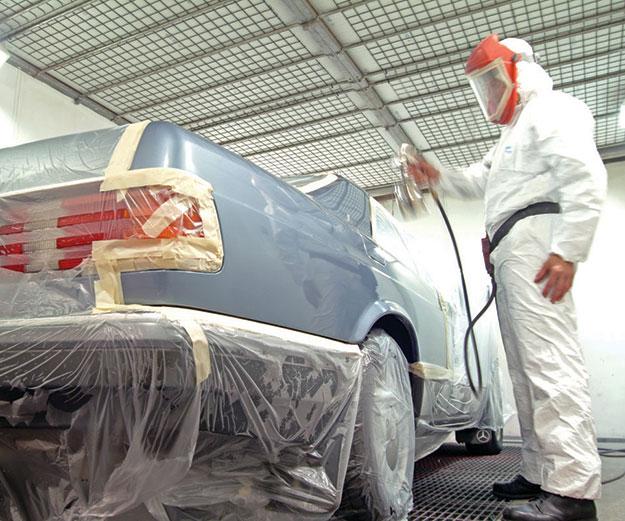 man spray painting a car in an auto body shop