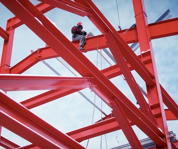 man sitting on red painted steel girders