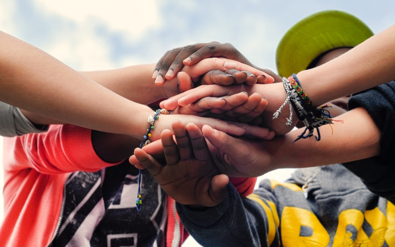a diverse group of teenagers joining hands together in cooperation