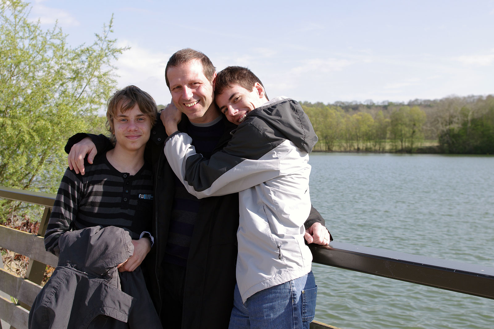A smiling father with his arm around his two sons on a bridge in a park