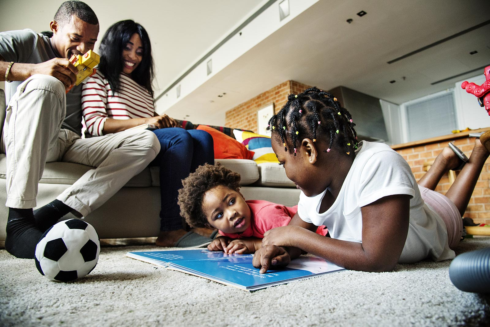 Young family at home with two young daughters playing together on the floor