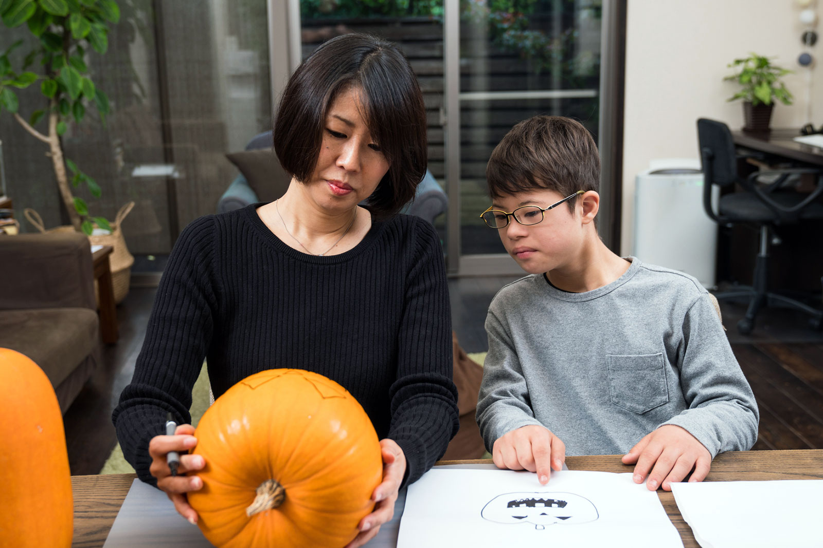 Asian mother helping disabled son prepare a pumpkin for carving