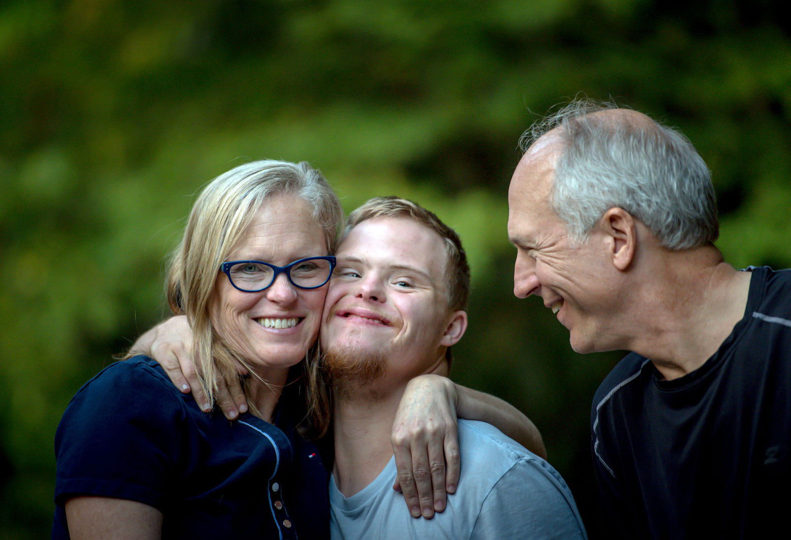 Smiling close up portrait of mother, father and developmentally disabled son