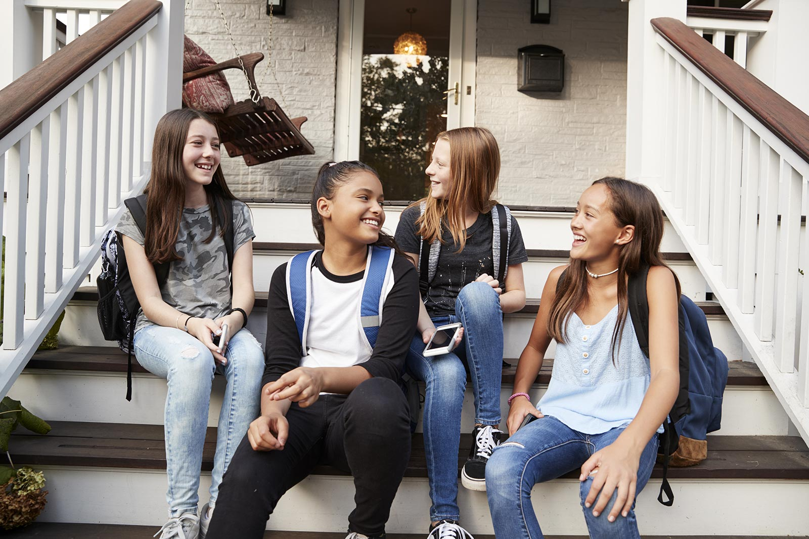 A group of 4 teenage girls chatting on the front steps of a house after school