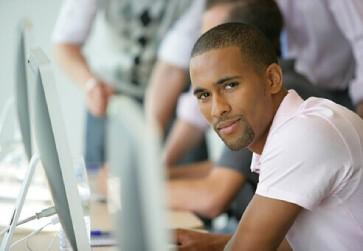 homme assis a un bureau equipe avec ordinateur