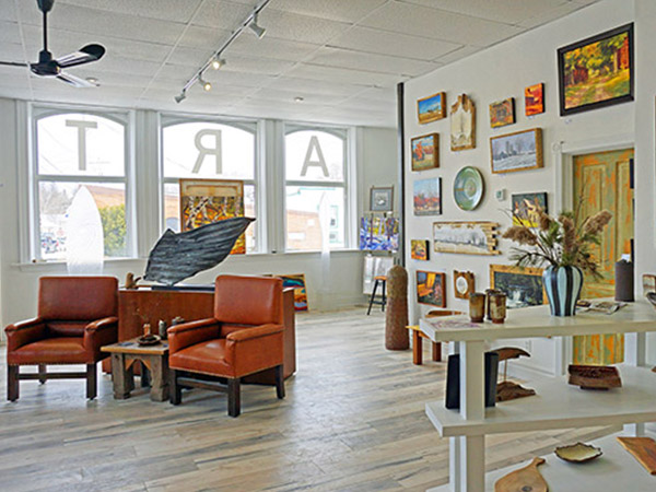 inside gallery showing leather chairs and art on walls