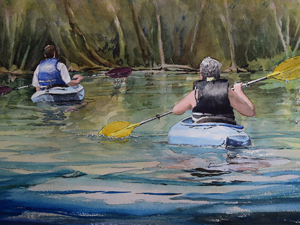 two kayakers paddling in a river