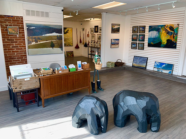 inside view of gallery with two elephant sculptures and paintings