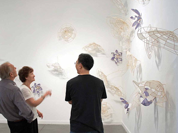 a couple looking at artwork and speaking to the artist