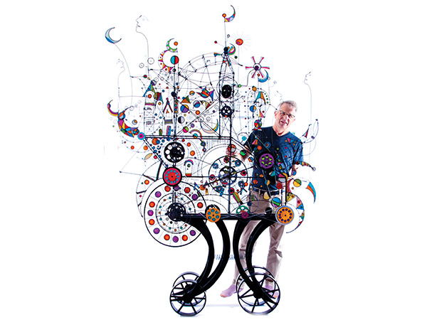 large mechanical sculpture with james standing beside it