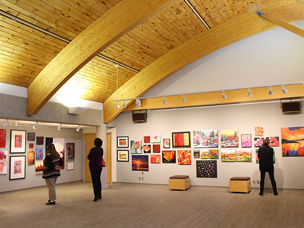 interior of gallery space,paintings on the walls and 3 people looking at the artwork.