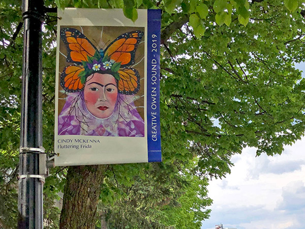One artwork reproduced on a banner hanging from a pole.