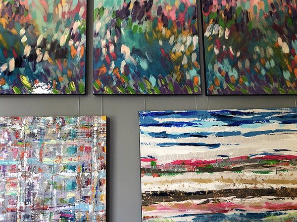 partial view of abstract paintings hanging on wall.