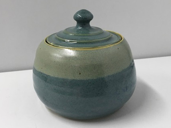 two shades of green pottery canister with lid.