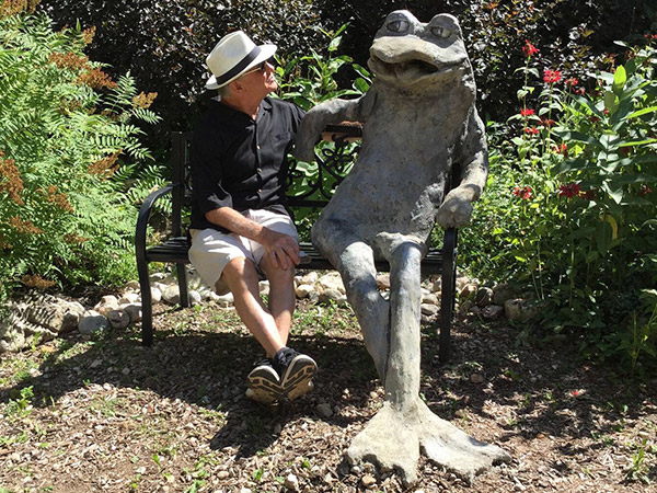 Sculpture of frog sitting on a bench with a real man.