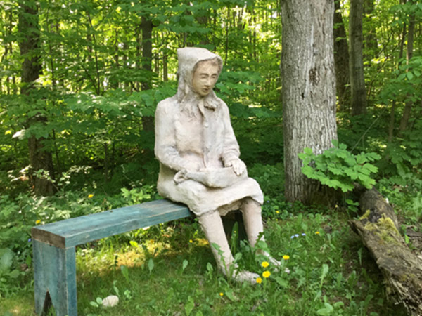 Sculpture of a woman sitting on a bench.