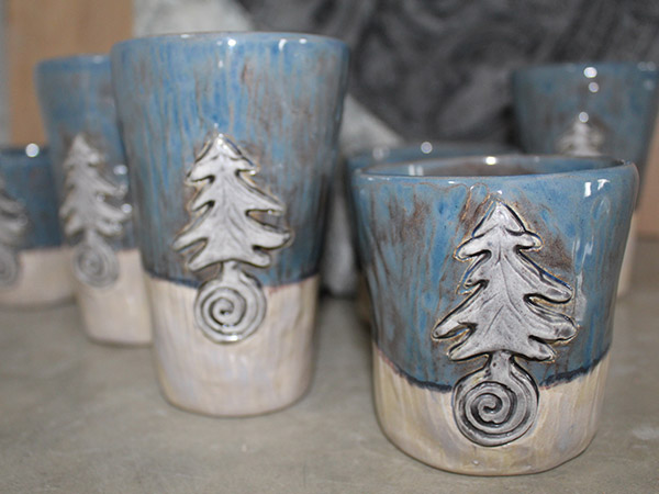 Blue pottery cups with evergreen tree applied image.