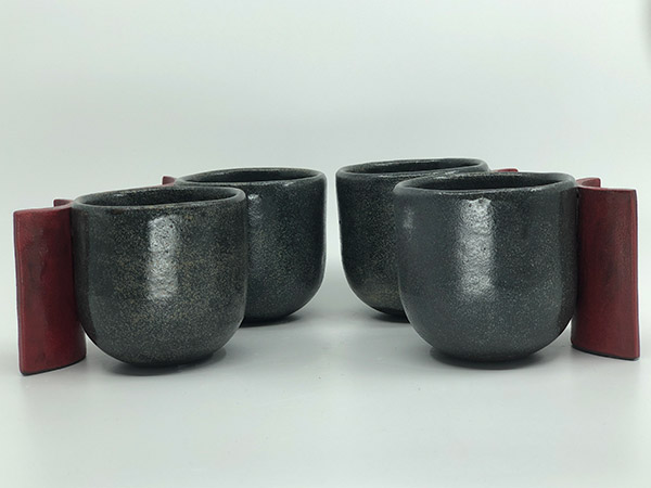 Four grey pottery mugs with unique handles.