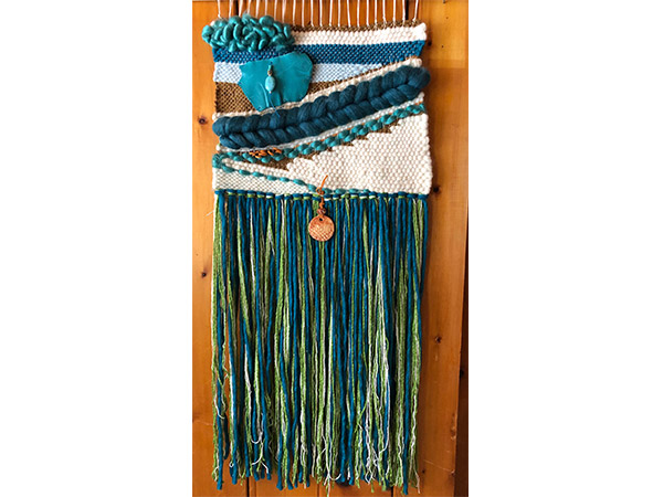 wall hanging woven with green and blue yarn.