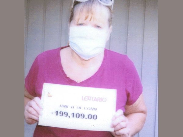 Southgate woman wins lottery holds cheque of over $199,000.