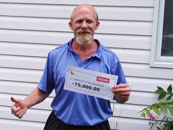 James Woodbridge stands outside with paper saying $75,000.