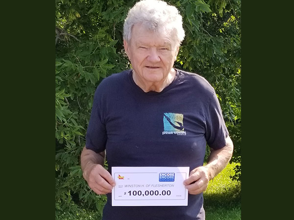 Hawkins holds his $100,000 lottery cheque.